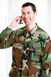 White male in army uniform on cell phone smiling