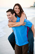 young happy couple holding hands on beach