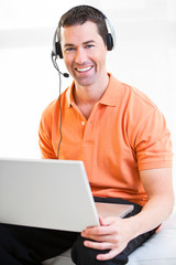 Happy business male on laptop with headset on smiling