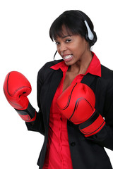 Businesswoman wearing a headset and boxing gloves