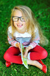 Adorable little girl in glasses holding book and laughing - outd