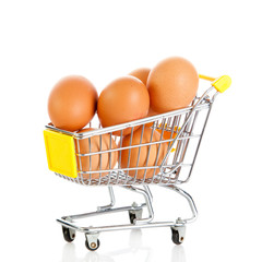 Eggs in the shopping cart isolaten in white. Brown eggs in the b
