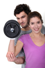 coach and young woman all smiles lifting weight