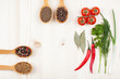 Spices, cherry tomatoes, chili, bay leaf on wood background