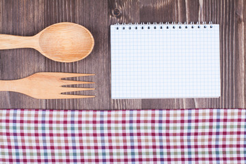 Recipe notebook, tablecloth, spoon, fork on wood background