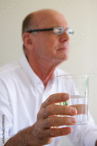 Elderly man taking medication with glass of water