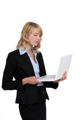 Blond businesswoman stood with laptop