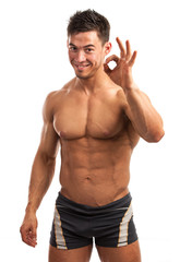 Muscular young man showing the ok sign isolated over white