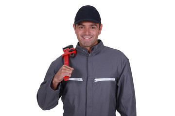 Cheerful plumber resting wrench on shoulder