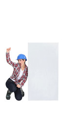 Excited female builder kneeling by blank poster