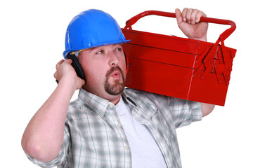 craftsman wearing headphones and carrying a tool box