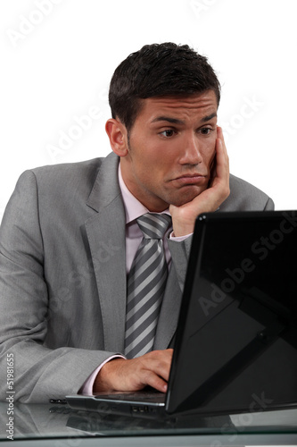 Perplexed man looking computer