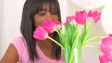 Happy black woman arranging flowers