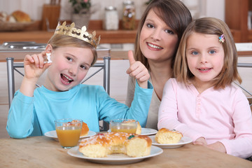 Mother and two daughters eating cake