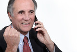 mature businessman on the phone clenching his fist