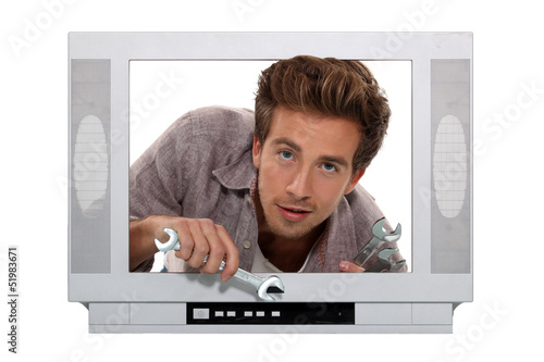 Concept shot of a young man trying to fix a television
