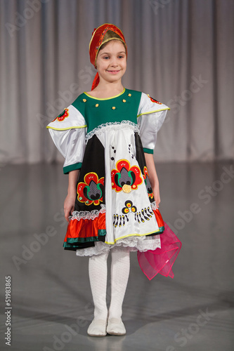smiling little girl in folk costume with wrap performs on stage.
