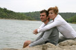 Couple sat by lake