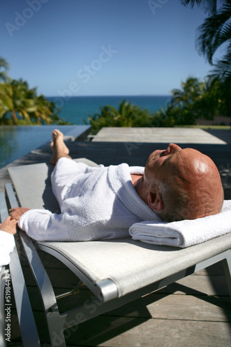 Old man laying on poolside sun lounger