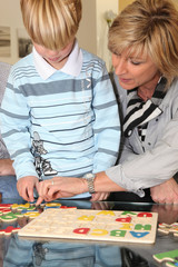 Grandmother helping her grandson with a puzzle