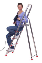 Woman sitting on stairs with drill