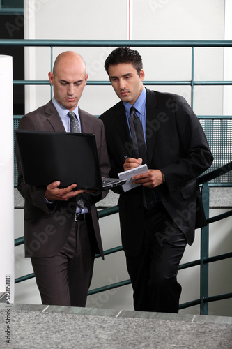 Businessmen comparing notes in stairwell