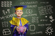 Happy scholar dressed toddler with piggybank