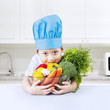 Boy chef holds bowl of vegetarian food