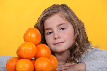 little stood with pile of oranges