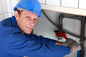 Plumber using a wrench on a water pipe