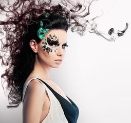 face art of rhinestones on brunette woman and smoke