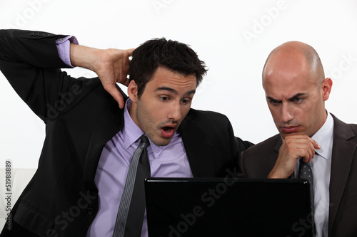 Two shocked office workers holding laptop