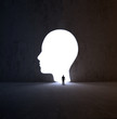 Man walking into a head-shaped opening in a wall