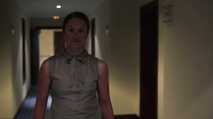 Young happy businesswoman walking in hall, steadicam shot