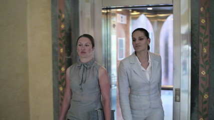 Two businesswomen walking out of the elevator, steadicam shot