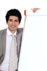 businessman posing next to a blank board