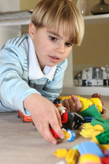Little blond boy playing with toys