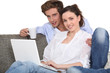 Couple using a laptop on a sofa