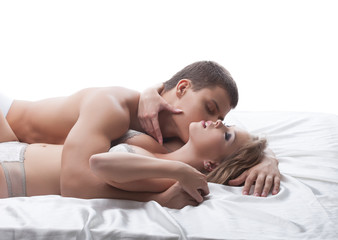 Sensual couple posing kissing in bed