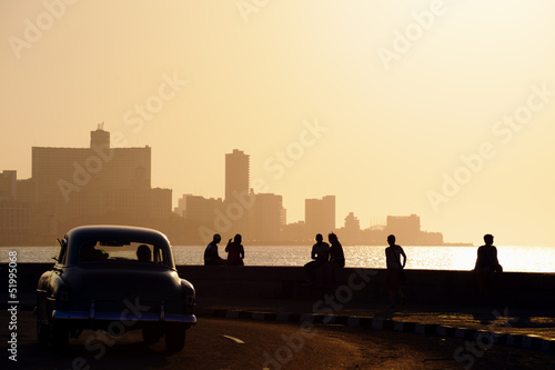 In de dag Oude auto s People and skyline of La Habana, Cuba, at sunset