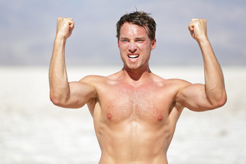 Fitness man showing muscles cheering outside