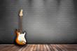 Raum mit Holzboden, Ziegelwand und E-Gitarre sunburst
