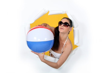 Woman with beach ball coming out of hole