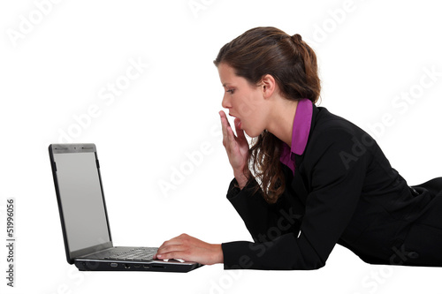 Woman yawning in front of a computer