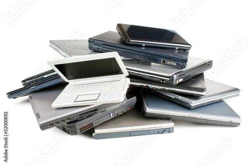 Stack of different sized and aged laptops, isolated