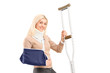 A happy blond female with broken arm holding a crutch
