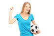 A happy female fan holding a football and gesturing