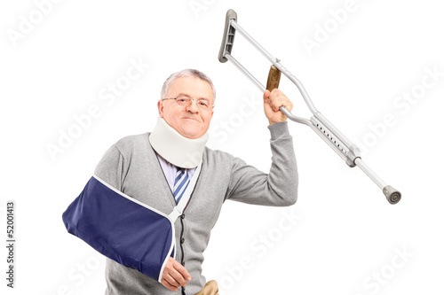 A happy mature gentleman with broken arm holding a crutch