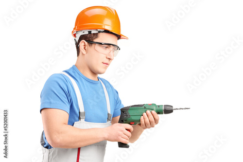 A manual worker with helmet using a drill tool