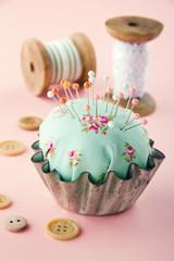 Green pincushion in an old metal cupcake